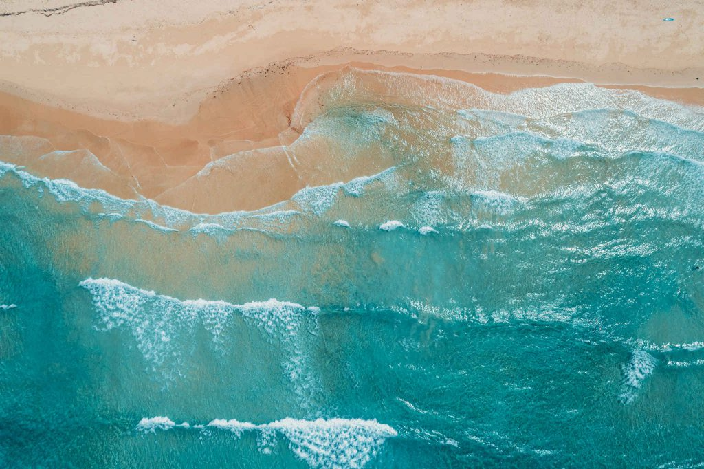 Surface waves. Aerial view to tropical sandy beach and blue ocean. Top view of ocean waves reaching shore on sunny day. Palawan, Philippines.