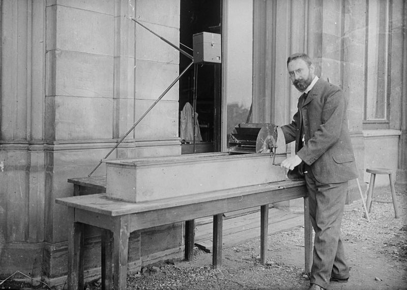 Ludwig Prandtl (1875-1953) in front of his research water channel in Hannover in 1904. The water was propelled with a hand-operated paddlewheel along the 1.5-meter long duct. A series of blades and meshes streamlined the flow adequately.
