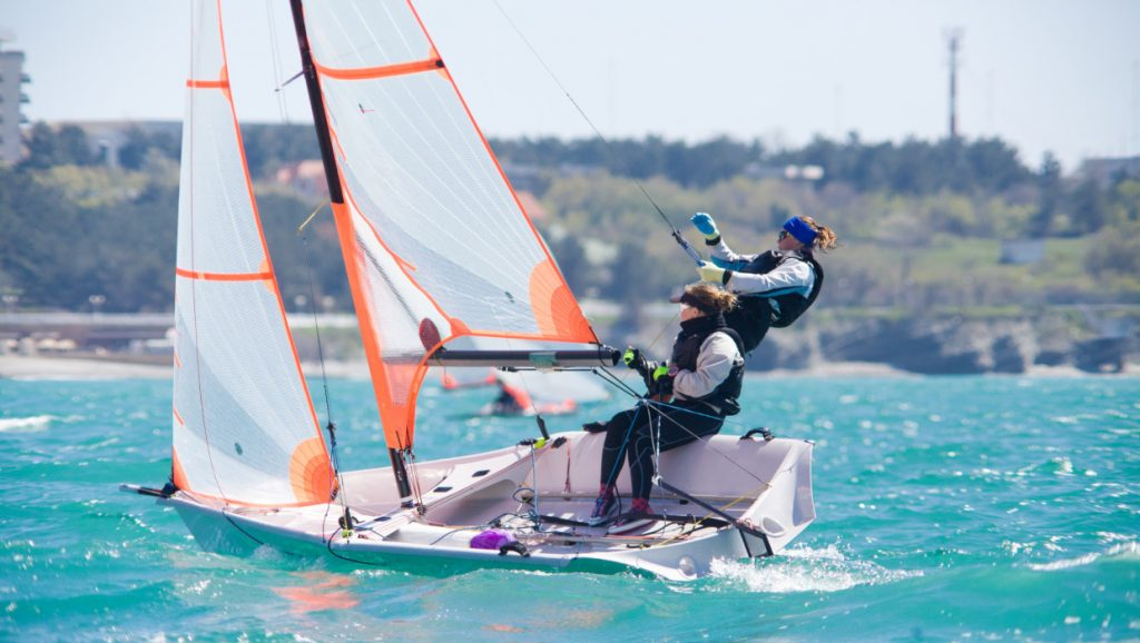 A team of two girls deftly managed to sail in the sea.